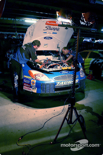 The Roush Racing crew of Kurt Busch work late into the night on the Sharpie Ford Taurus