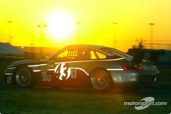 The #43 Porsche races past the rising sun on Sunday morning