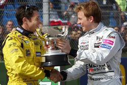 Giancarlo Fisichella receives the winner's trophy for the Brazilian GP from Kimi Raikkonen
