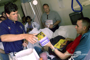 Michael Waltrip hands Pfc. Dennis Wallace some gifts during a visit by seven NASCAR drivers to Walter Reed Army Medical Center in Washington, D.C. as Ken Schrader looks on
