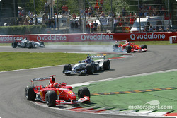 First lap: Michael Schumacher leads Juan Pablo Montoya while Rubens Barrichello locks the tires