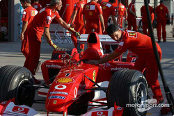 Ferrari team members push car on pitlane