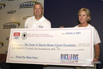 Dale Jarrett presents a check to Cindy Schneible for the Susan G. Komen Breast Cancer Foundation