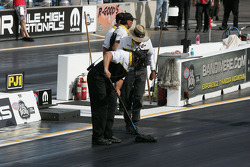 NHRA Officals clean the track between runs during