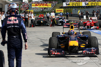 Sebastian Vettel, Red Bull Racing walks out of parc ferme as Mark Webber, Red Bull Racing the winner drives in