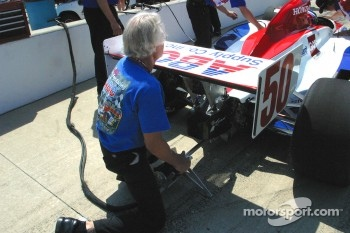 A crew member for Al Unser Jr. prepares to start the car