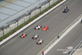 All the cars that A.J. Foyt drove to victory here at the Indianapolis Motor Speedway come down the main straight on the ceremonial lap