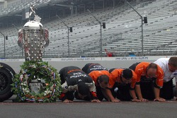 Dario Franchitti and his crew kiss the bricks at the start/finish line