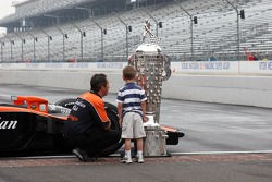 An Andretti-Green employee admires the Borg Warner Trophy with his son