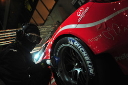 A Luxury Racing Ferrari mechanic checks tire pressure