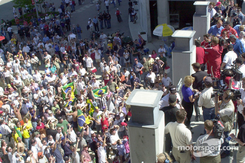 The crowd cheering Castroneves, and Helio playing to the crowd