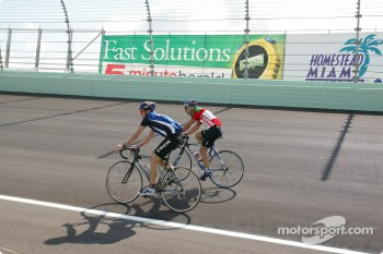 Tony Kanaan on bicycle with two time Ironman Triathalon World Champion Tim DeBoon