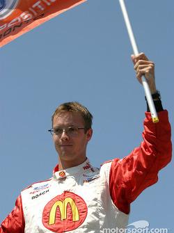 Pole winner Sébastien Bourdais celebrates with the flag