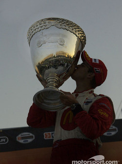 2004 Champ Car World Series champion Sébastien Bourdais kisses the Vanderbilt Cup as the sun sets