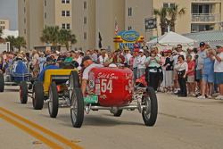 Historic cars drive past fans at the North Turn
