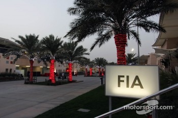 FIA building sign glowing in the paddock as dusk falls