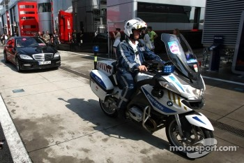 Bernie Ecclestone, arrives at the track with a police escort