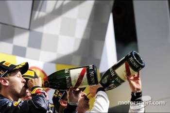Race winner Jenson Button, McLaren celebrates on the podium with Sebastian Vettel, Red Bull Racing