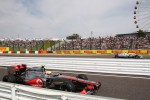 Lewis Hamilton, McLaren enters the pits as Nico Rosberg, Mercedes AMG F1 passes on track