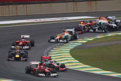 Felipe Massa, Ferrari leads Jenson Button, McLaren as Sebastian Vettel, Red Bull Racing survives a crash with Sergio Perez, Sauber and Bruno Senna, Williams at the start of the race