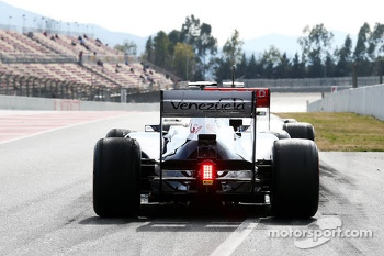 Pastor Maldonado, Williams FW35 and Sergio Perez, McLaren MP4-28 at the pit lane exit