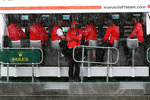 Marc Hynes, Marussia F1 Team Driver Coach watches the rain fall from the pit gantry