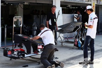 Esteban Gutierrez, Sauber C32 looks at a Sauber C32 front wing being prepared by a mechanic