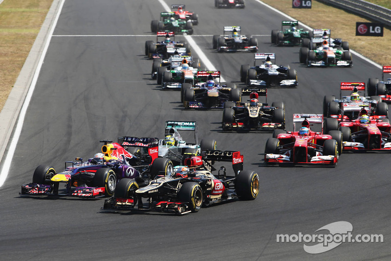 Sebastian Vettel, Red Bull Racing RB9 and Romain Grosjean, Lotus F1 E21 battle at the start of the race