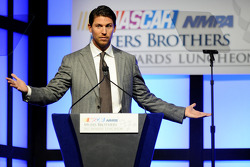 Denny Hamlin speaks onstage after winning the Coors Light Pole Award at the NMPA Myers Brothers Awards Luncheon