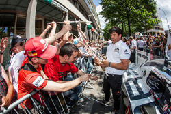 Porsche team members give away flags to fans