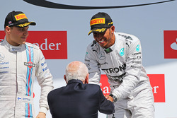 Race winner Lewis Hamilton, Mercedes AMG F1 celebrates on the podium with John Surtees