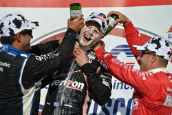 Race winner Will Power gets a face full of cream puff and champagne bath from second place Juan Pablo Montoya and third place Tony Kanaan