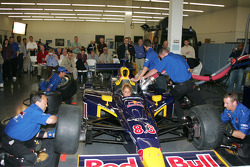 Red Bull Cheever Racing crew members perform a pit stop for media members at the team's shop