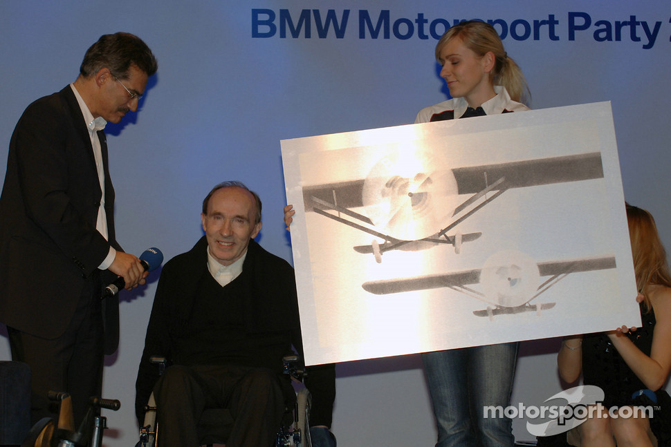 Dr Mario Theissen (BMW Motorsport Director) presents Team Principal Frank Williams with a going away present