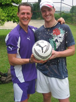 Michael Schumacher and Ralf Schumacher play football
