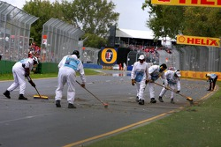 Course marshalls clean up the track after the crash of Vitantonio Liuzzi
