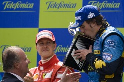 Podium: race winner Fernando Alonso receives his trophy from King of Spain Juan Carlos
