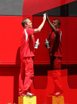 A Scuderia Ferrari team member cleans the trucks