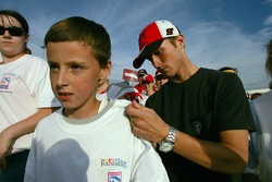 Kasey Kahne signs the t-shirt of a young fan during a charity walk benefiting the NASCAR Foundation at Dover International Speedway