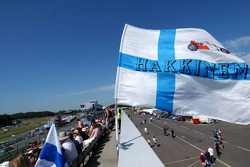 Dedicated fans of Mika Hakkinen wave the Finish flag on the grandstand