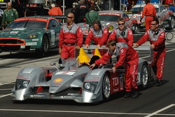 Audi Sport North America team members roll the #2 Audi R10 TDI Power through pit row