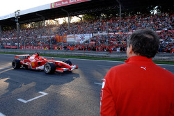 Jean Todt looks on as Michael Schumacher drives by
