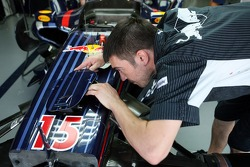 A Red Bull Racing pit crew member working on the car of Mark Webber