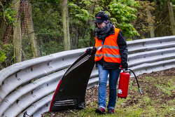 A course marshal cleans up the track