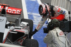 Race winner Fernando Alonso points to where his car touched Felipe Massa