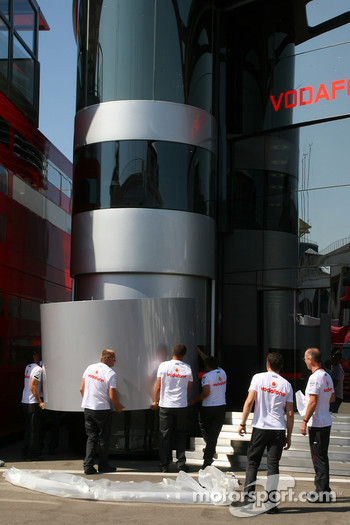 McLaren Mercedes team members install a panel onto the side of their motorhome
