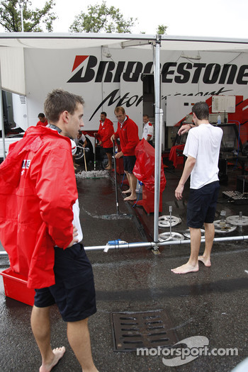 Bridgestone team members try to dry up their paddock area