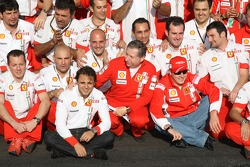 Race winner Kimi Raikkonen celebrates with Felipe Massa and Ferrari team members