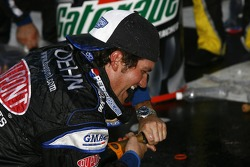 Victory lane: a crew member has problems with his bottle of champagne