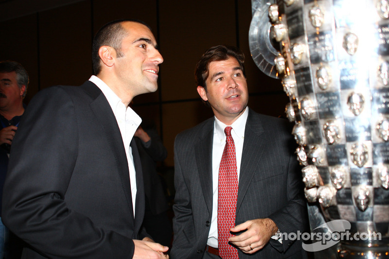Dario Franchitti, left, and IMS President and Chief Operating Officer Joie Chitwood admire the winning drivers' images on the Borg-Warner Trophy